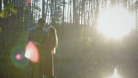 A romantic couple stands and kisses near the lake, and between them the rays of the sun, sunlight stock video footage