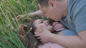 Romantic couple in summer on a glade. The girl lies in the grass among white dandelions. The guy touches the girl`s hair stock footage