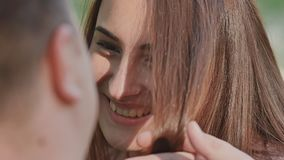 Romantic couple in summer on a glade. The hand of the enamored guy touches his girl`s hair. They look at each other. Happy smile on girl face. Tenderness stock footage