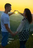 Romantic couple at sunset make a heart shape from hands, the rays shine through hands, beautiful landscape and bright yellow sky, Stock Photo