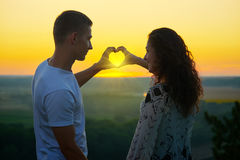 Romantic couple at sunset make a heart shape from hands, the rays of sun shine through hands, beautiful landscape and bright yello Stock Images