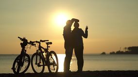 Romantic couple at sunset. Silhouette of bicycles on sunset. stock video footage