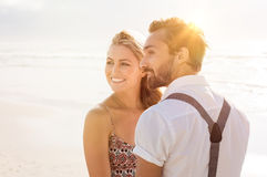 Romantic couple at sunset. Romantic couple together at beach. Carefree couple on the beach in casual clothing at sunset. Young couple looking away Stock Photo