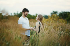 Romantic Couple at Sunset. Two people in love at sunset or sunrise. Man and woman on field Stock Photography