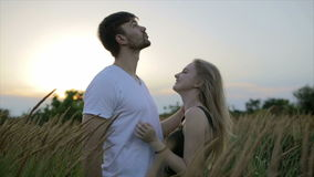 Romantic Couple at Sunset. Two people in love at sunset or sunrise. Man and woman kissing on field stock video footage