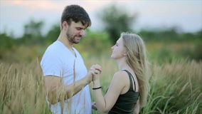 Romantic Couple at Sunset. Two people in love at sunset or sunrise. Man and woman kissing on field stock footage