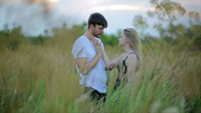 Romantic Couple at Sunset. Two people in love at sunset or sunrise. Man and woman kissing on field stock video