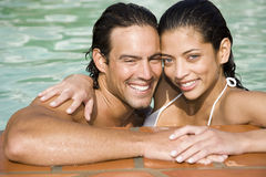 Romantic couple in a swimming pool on summer holiday royalty free stock images