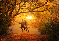 Romantic couple swing in the autumn park.