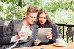 Romantic couple with a tablet at the cafe on a blurred background. Romance concept. Copy space. Stock Photos
