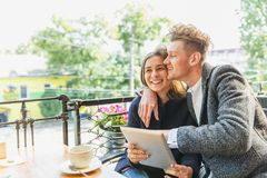Romantic couple with a tablet at the cafe on a blurred background. Romance concept. Copy space. Royalty Free Stock Image