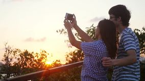 Romantic couple taking selfie video by sunset during vacation. Slow motion. Woman and man taking cell phone photos stock video
