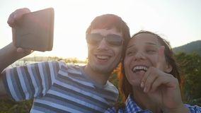 Romantic couple taking selfie video by sunset during vacation. Slow motion. 1920x1080 stock video