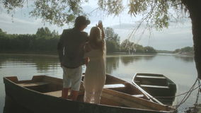 Romantic couple talking in old boat on sunset stock video