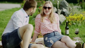 Romantic couple talking. And smiling spending sunny day on a picnic with red wine stock video footage