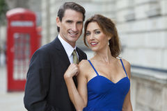 Romantic Couple by Telephone Box, London, England. Romantic men and women couple by a traditional red phone box, London, England, Great Britain Stock Photo