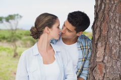 Romantic couple about to kiss by tree trunk Royalty Free Stock Photo
