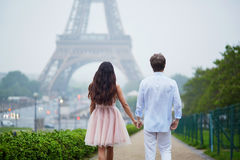 Romantic couple together in Paris. Beautiful romantic couple in love near the Eiffel tower in Paris on a cloudy and foggy rainy day, back view Royalty Free Stock Image