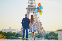 Couple in Paris with bunch of balloons looking at Eiffel tower royalty free stock photography