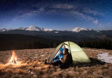Romantic couple tourists having a rest in the camping at night under beautiful night sky full of stars and milky way Stock Photos