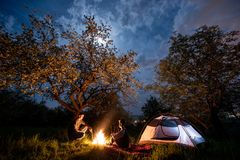 Couple tourists sitting at a campfire near tent under trees and night sky with the moon. Night camping Royalty Free Stock Photos