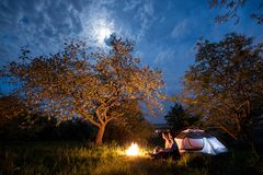 Romantic couple tourists sitting at a campfire near tent under trees and night sky with the moon Stock Photography