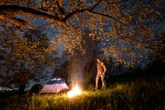 Romantic couple tourists standing at a campfire near tent, hugging each other under trees and night sky. Night camping Stock Image