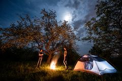 Couple tourists standing at a campfire near tent under trees and night sky with the moon. Night camping Royalty Free Stock Image