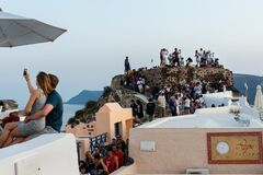 Romantic couple tourists taking selfie photo in Santorini sunset point Greece. Wish list for year 2021