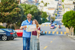 Romantic couple of tourists using map in San Francisco, California, USA Stock Photos