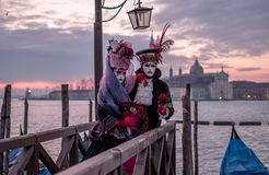 Romantic couple in traditional costume and masks standing with back to the Grand Canal and San Giorgio, Venice, Italy stock image