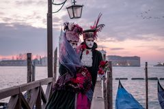 Romantic couple in traditional costume and masks at sunrise, standing with back to the Grand Canal and San Giorgio, Venice, Italy royalty free stock images