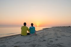 Romantic couple of travelers is sitting on the beach. And admiring setting sun over the sea. Back view Stock Photography