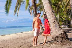 Romantic couple at tropical beach near palm tree Royalty Free Stock Image