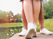 Romantic couple of two teenagers kissing on the pier near lake i Stock Photography