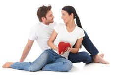 Romantic couple at Valentine's day smiling. Romantic couple making eyes at each other, holding red pillow heart, smiling Stock Image