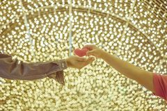 Romantic couple on valentines day. Happy joyful woman giving man heart shape little pillow with decorate colorful light bulbs in stock images