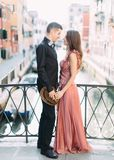 Romantic couple in Venice. Young beautiful couple standing on bridge of the Venice canal and hugging. Italy, Europe. stock image