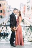 Romantic couple in Venice. Young beautiful couple standing on bridge of the Venice canal and hugging. Italy, Europe. royalty free stock image