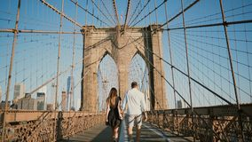 Romantic couple walk along Brooklyn Bridge NYC, hold hands and kiss on a beautiful summer day, back view low angle 4K. Adult man and woman share lovely bonding stock footage