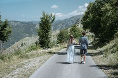 Romantic couple walking along the road against the background o. F the mountains. Slow motion royalty free stock photos
