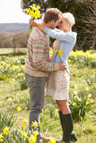 Romantic Couple Walking Amongst Spring Daffodils. In the sun Stock Photo