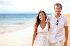 Romantic couple walking on beach. On honeymoon travel vacation summer holidays romance. Young happy lovers, Asian women and Caucasian men holding hands Stock Image