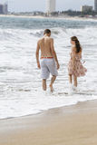 Romantic couple walking on the beach. Man and woman in love. Stock Photos