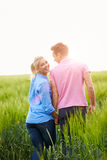 Romantic Couple Walking In Field Holding Hands Royalty Free Stock Photos