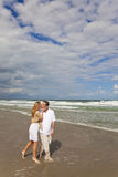 Romantic Couple Walking and Kissing On A Beach. A young man and woman walking and kissing as a romantic couple on a beach Stock Images