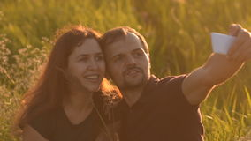 Romantic couple walking in the Park at sunset and makes a selfie stock video footage