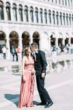 Romantic couple walking on Piazza San Marco in Venice. Pretty girl in pink dress and handsome boy in black clothes royalty free stock photography