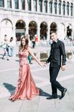 Romantic couple walking on Piazza San Marco in Venice. Pretty girl in pink dress and handsome boy in black clothes stock image
