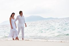 Romantic couple walking on the sea shore Royalty Free Stock Photos
